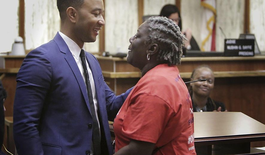 Singer songwriter John Legend, left,  greets Carmen Brown who was the first person called up in a special court hearing aimed at restoring her right to vote under Florida's amendment 4, Friday, Nov. 8, 2019, in Miami. (Jose A. Iglesias/Miami Herald via AP)