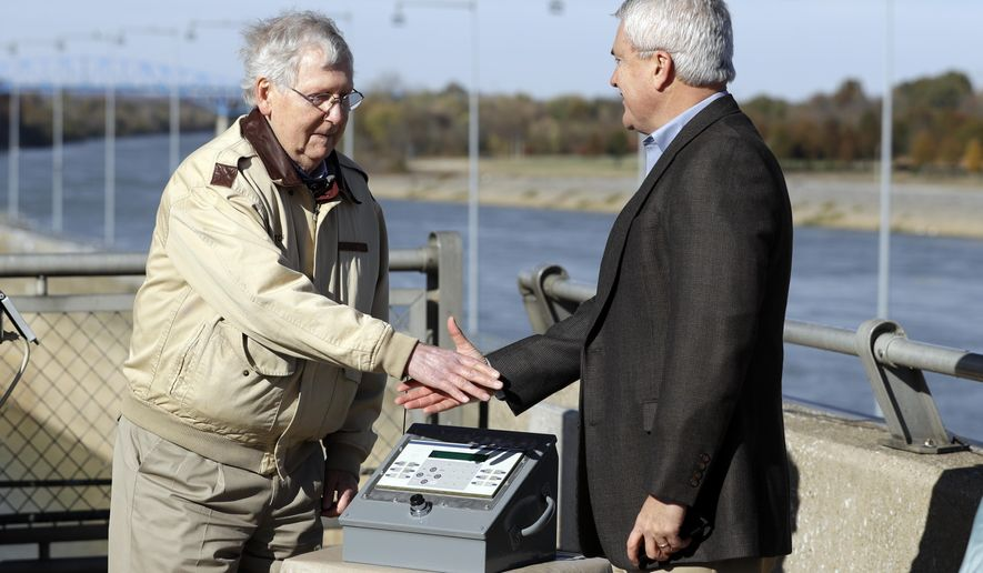 Sen. Mitch McConnell, R-Ky., left, and Rep. James Comer, R-Ky., shake hands after pressing the power button for a bio-acoustic fish fence at the Barkley Lock and Dam where the Cumberland River meets Lake Barkley Friday, Nov. 8, 2019, in Grand Rivers, Ky. The noise-making, bubbling barrier has been installed in the lock to deter the spread of destructive Asian carp . (AP Photo/Mark Humphrey)