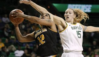 Grambling State guard Justice Coleman (12) goes up to shoot as Baylor forward Lauren Cox (15) defends in the first half of an NCAA college basketball game in Waco, Texas, Friday, Nov. 8, 2019. (AP Photo/Tony Gutierrez)