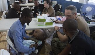 A man holds an ill baby as he sits with US military doctors who arrived on the U.S. Navy hospital ship USNS Comfort, as Haitians get free treatment, at the Killick Coast Guard Base, in Port-au-Prince, Haiti, Friday, Nov. 8, 2019. Haitians are getting free access to U.S. military doctors from the ship on a first-come, first-serve basis for general, pediatric, dental, ophthalmological and orthopedic care. (AP Photo/Dieu Nalio Chery)