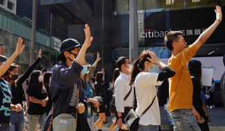 Protesters hold up their hands to represent their five demands as they take part in a memorial flash mob in Hong Kong on Friday, Nov. 8, 2019. A Hong Kong university student who fell off a parking garage after police fired tear gas during clashes with anti-government protesters died Friday, in a rare fatality after five months of unrest that intensified anger in the semi-autonomous Chinese territory. (AP Photo/Vincent Yu)