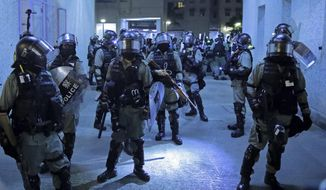 Police officers at a housing estate after clashing with protesters in Hong Kong, early Saturday, Nov. 9, 2019. A Hong Kong university student who fell off a parking garage after police fired tear gas during clashes with anti-government protesters died Friday in a rare fatality in five months of unrest, fueling more outrage against authorities in the semi-autonomous Chinese territory. (AP Photo/Kin Cheung)