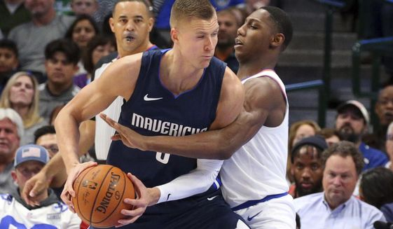 Dallas Mavericks forward Kristaps Porzingis (6) is guarded by New York Knicks guard RJ Barrett (9) in the first half of an NBA basketball game Friday, Nov. 8, 2019, in Dallas. (AP Photo/Richard W. Rodriguez)