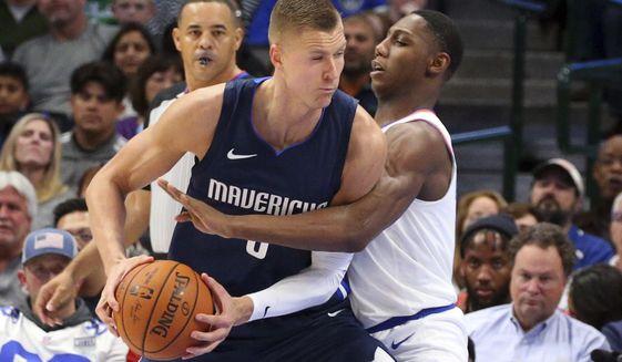 Dallas Mavericks forward Kristaps Porzingis (6) is guarded by New York Knicks guard RJ Barrett (9) in the first half of an NBA basketball game Friday, Nov. 8, 2019, in Dallas. (AP Photo/Richard W. Rodriguez)
