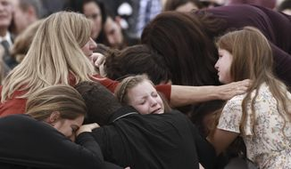 Family and friends weep during the funeral service for Dawna Ray Langford, 43, and her sons Trevor, 11, and Rogan, 2, who were killed in an ambush earlier this week, in La Mora, Mexico, Thursday, Nov. 7, 2019. As Mexican soldiers stood guard, the three were laid to rest in a single grave at the first funeral for the victims of a drug cartel ambush that left nine American women and children dead. (AP Photo/Christian Chavez)
