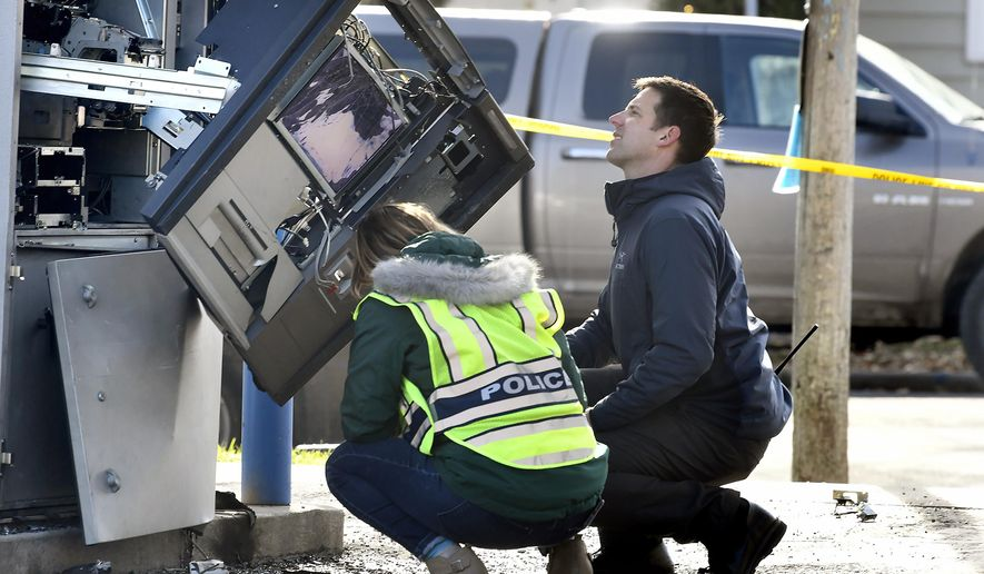 Police officers investigate an automated teller machine that exploded at the First Security Bank in Missoula, Mont., Thursday, Nov. 7, 2019. Two people have been detained. Witnesses reported seeing a man in a gray minivan pour liquid on the ATM and ignite it, causing an explosion. The ATM was damaged, but no injuries were reported. (Tommy Martino/The Missoulian via AP)