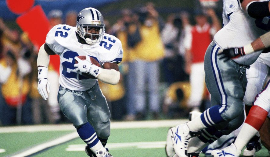FILE - In this Jan. 30, 1994, file photo, Dallas Cowboys running back Emmitt Smith (22) runs for short yardage against the Buffalo Bills during Super Bowl XXVIII action at the Georgia Dome in Atlanta. The NFL became a truly booming business in the 1990s, with multi-billion-dollar TV contracts, expansion to 30 teams, and a late-decade wave of new stadiums. Players began to pick up a bigger share of the wealth, with the dawn of unrestricted free agency. The results on the field were largely dominated by the NFC, with Smith and the Cowboys, Steve Young and the San Francisco 49ers, and Brett Favre and the Green Bay Packers enjoying the most success. (AP Photo/Susan Ragan, File)