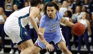 North Carolina's Cole Anthony (2) brings the ball upcourt against UNC Wilmington 's Kai Toews (10) during the first half of an NCAA college basketball game in Wilmington, N.C., Friday, Nov. 8, 2019. (AP Photo/Karl B DeBlaker)