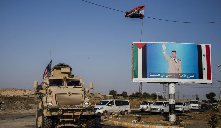 FILE - In this Saturday, Oct. 26. 2019 file photo, a U.S. military vehicle drives south of the northeastern city of Qamishli, likely heading to the oil-rich Deir el-Zour area where there are oil fields, or possibly to another base nearby, as it passes by a poster showing Syrain President Bashar Aassad. President Donald Trump's decision to dispatch new U.S. forces to eastern Syria to secure oil fields is being criticized by some experts as ill-defined and ambiguous. But the residents of the area, one of the country's most remote and richest regions, hope the U.S. focus on eastern Syria would bring an economic boon and eliminate what remains of the Islamic State group. (AP Photo/Baderkhan Ahmad, File)