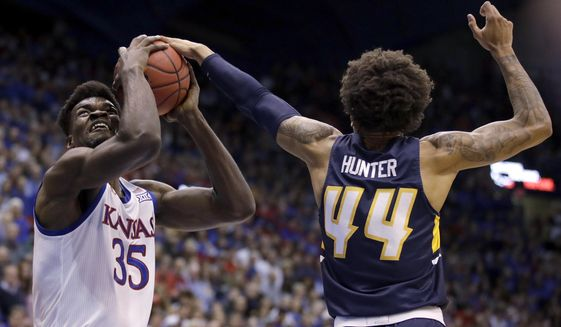 UNC Greensboro's Kaleb Hunter (44) tries to block a shot by Kansas' Udoka Azubuike (35) during the first half of an NCAA college basketball game Friday, Nov. 8, 2019, in Lawrence, Kan. (AP Photo/Charlie Riedel)