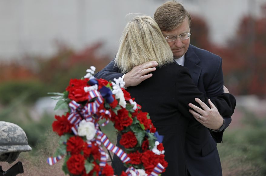 Republican Gov.-elect Tate Reeves, hugs Jenny Smith, a Gold Star mother, following a Veterans Day ceremony at the Museum of Mississippi History and Mississippi Civil Rights Museum in Jackson, Miss., Nov. 8, 2019. Smith and her husband Eddie Smith, lay a memorial wreath on Entergy Plaza outside the museums, honoring all veterans and her late son, Marine Staff Sgt. Jason A. Rogers, who was killed in an explosion two days before what would have been his 29th birthday, in April 7, 2011. (AP Photo/Rogelio V. Solis)