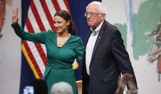 Rep. Alexandria Ocasio-Cortez, D-N.Y stands alongside Democratic presidential candidate Sen. Bernie Sanders, I-Vt., during a campaign rally on Saturday, Nov. 9, 2019, at Drake University in Des Moines, Iowa.  (Bryon Houlgrave /The Des Moines Register via AP)