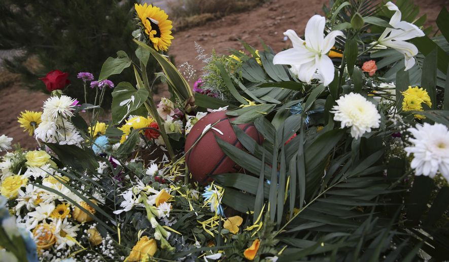 A basketball sits on a bed of flowers decorating the grave that contain the remains of 12-year-old Howard Jacob Miller Jr. at the cemetery in Colonia LeBaron, Mexico, Saturday, Nov. 9, 2019. U.S. citizens living in a small Mexican farming community established by their Mormon ancestors are trying to decide whether they should stay or leave after burying some of the nine American women and children, including Howard, slaughtered this week in a drug cartel ambush. (AP Photo/Marco Ugarte)