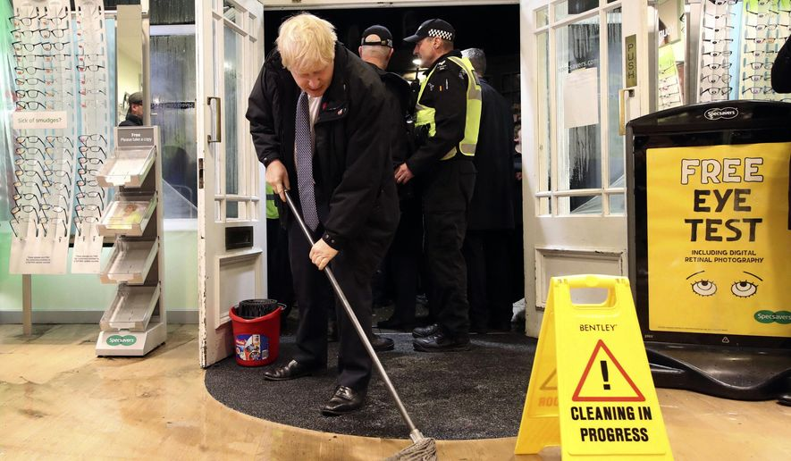 Britain's Prime Minister Boris Johnson visits an optician shop after flooding, in Matlock, north England, Friday Nov. 8, 2019. A woman died after being swept away by surging waters as torrential rain drenched parts of north and central England, swelling rivers, forcing evacuations and disrupting travel for a second day Friday.(Danny Lawson/PA via AP)