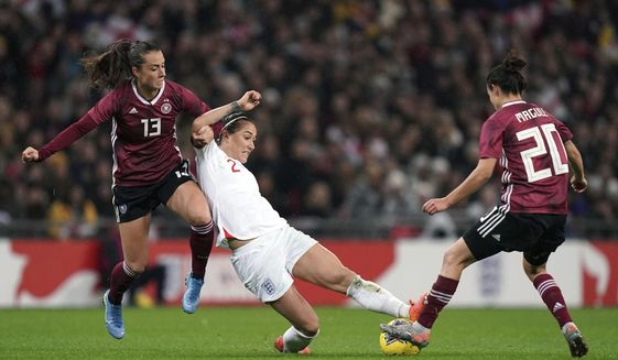 Germany's Sara Dabritz, left and Lina Magull, right, battle for the ball with England's Lucy Bronze , during the Women's International Friendly soccer match between England and Germany, at Wembley Stadium, in London, Saturday, Nov. 9, 2019. (John Walton/PA via AP)