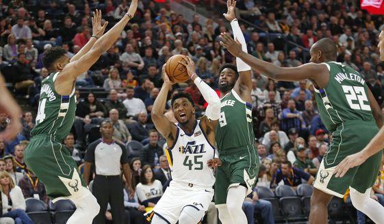 Utah Jazz guard Donovan Mitchell (45) drives to the basket as Milwaukee Bucks' Wesley Matthews (9), Giannis Antetokounmpo (34) and Khris Middleton (22) defend during the first half of an NBA basketball game Friday, Nov. 8, 2019, in Salt Lake City. (AP Photo/Rick Bowmer)