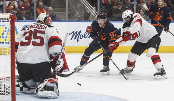 New Jersey Devils goalie Cory Schneider (35) makes the save on Edmonton Oilers' Connor McDavid (97) as P.K. Subban (76) defends during the second period of an NHL hockey game Friday, Nov. 8, 2019, in Edmonton, Alberta. (Jason Franson/The Canadian Press via AP)