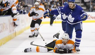Philadelphia Flyers center Tyler Pitlick (18) watches the puck as Toronto Maple Leafs center Alexander Kerfoot (15) loses his stick during the second period of their NHL hockey game in Toronto, Saturday, Nov. 9, 2019. (Cole Burston/The Canadian Press via AP)