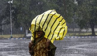 A woman covers her head with a plastic sheet as it rains in Kolkata, India, Saturday, Nov. 9, 2019. Authorities in nearby Bangladesh put more than 50,000 volunteers on standby and readied about 5000 shelters as a strong cyclone in the Bay of Bengal is expected to hit the low-lying nation's vast southwestern and southern coast on Saturday evening. (AP Photo/Bikas Das)