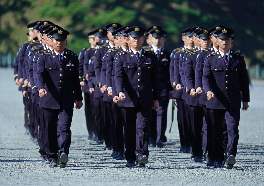 Police officers walk in formation as they stand guard at the Imperial Palace before the royal parade of Japanese Emperor Naruhito and Empress Masako in Tokyo, Sunday, Nov. 10, 2019. (AP Photo/Eugene Hoshiko)