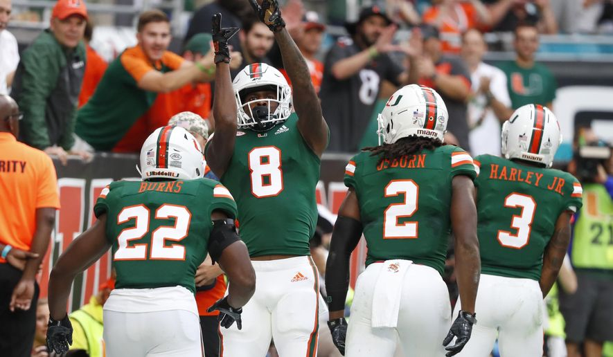 Miami wide receiver Dee Wiggins (8) celebrates his touchdown as he heads back to the sideline with teammates during the first half of an NCAA college football game against Louisville, Saturday, Nov. 9, 2019, in Miami Gardens, Fla. Others from left, Robert Burns, K.J. Osborn and Mike Harley. (AP Photo/Wilfredo Lee)