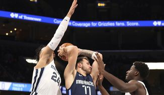 Memphis Grizzlies' Dillon Brooks (24) and Jaren Jackson Jr. (13) close in on Dallas Mavericks' Luka Doncic (77) during the first half of an NBA basketball game Saturday, Nov. 9, 2019, in Memphis, Tenn. (AP Photo/Karen Pulfer Focht)