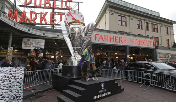 Fans wearing Seattle Sounders gear pose for a photo with a giant replica of the MLS Cup trophy, Friday, Nov. 8, 2019, at Pike Place Market in Seattle. Toronto FC is scheduled to face the Seattle Sounders on Sunday in the MLS Cup soccer match in Seattle, the third time the two teams will have met for the MLS championship. (AP Photo/Ted S. Warren)