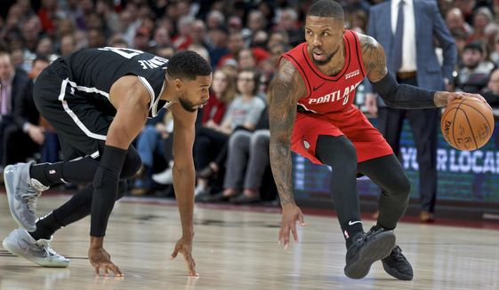 Portland Trail Blazers guard Damian Lillard, right, dribbles around Brooklyn Nets guard Garrett Temple during the first half of an NBA basketball game in Portland, Ore., Friday, Nov. 8, 2019. (AP Photo/Craig Mitchelldyer)
