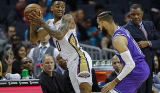New Orleans Pelicans guard Nickeil Alexander-Walker, left, looks to pass against Charlotte Hornets forward Cody Martin in the first half of an NBA basketball game in Charlotte, N.C., Saturday, Nov. 9, 2019. (AP Photo/Nell Redmond)