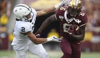 Minnesota wide receiver Tyler Johnson (6) holds onto the ball against Penn State cornerback Keaton Ellis (2) during an NCAA college football game, Saturday, Nov. 9, 2019, in Minneapolis. (AP Photo/Stacy Bengs)