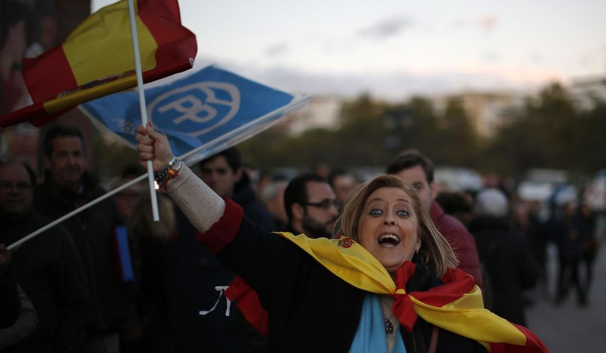 A woman waves a Spanish flag before the Popular Party closing election campaign event at Las Ventas bullring in Madrid, Spain, Friday, Nov. 8, 2019. Spaniards are voting Sunday for the fourth time in as many years to elect the prime minister who will face a renewed Catalan independence bid that has boosted support for the far-right elsewhere in the country. (AP Photo/Manu Fernandez)