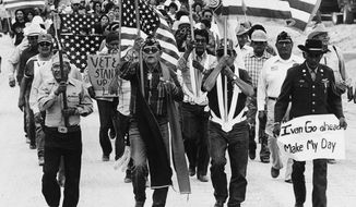 "In this July 8, 1986, file photo, World War II Navajo veterans and supporters march through the reservation in a show of solidarity against giving up any of their land to the Hopis in Arizona. ""The Warrior Tradition,"" a new film set to air on most PBS stations Monday, Nov. 11, 2019, examines the history of Native Americans in the U.S. military since World War I. (AP Photo/Jeff Robbins, File)"