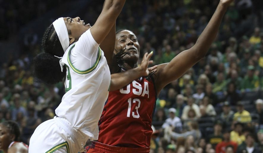 Oregon's Minyon Moore, left, is fouled while going to the basket by United States' Sylvia Fowles during the first half of an exhibition basketball game in Eugene, Ore., Saturday, Nov. 9, 2019. (AP Photo/Chris Pietsch)