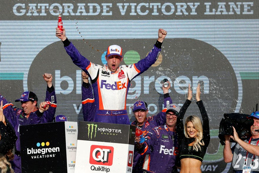 Denny Hamlin celebrates in Victory Lane after his NASCAR Cup Series race win in Avondale, Arizona, on Sunday. Hamlin advanced to next week's title race. (ASSOCIATED PRESS)