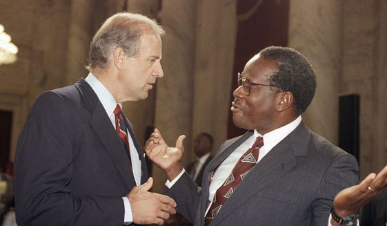 In this file photo, then-D.C. Circuit Court of Appeals Judge larence Thomas gestures while talking with Sen. Joseph Biden, D-Del., chairman of the Senate Judiciary Committee, during a break in the committee's Supreme Court nomination hearing for Thomas on Capitol Hill in Washington, Friday, Sept. 13, 1991. Associated Press) **FILE**