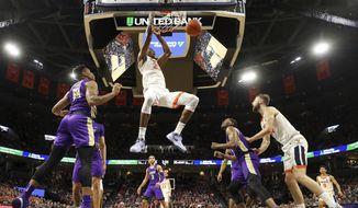 Virginia forward Mamadi Diakite (25) dunks between James Madison defenders during an NCAA college basketball game in Charlottesville, Va., Sunday, Nov. 10, 2019. Virginia won 65-34. (AP Photo/Andrew Shurtleff)