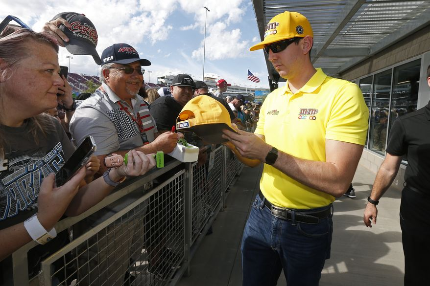 Driver Kyle Busch, right, gives autographs to fans prior to a NASCAR Cup Series auto race at ISM Raceway, Sunday, Nov. 10, 2019, in Avondale, Ariz. (AP Photo/Ralph Freso) ** FILE **