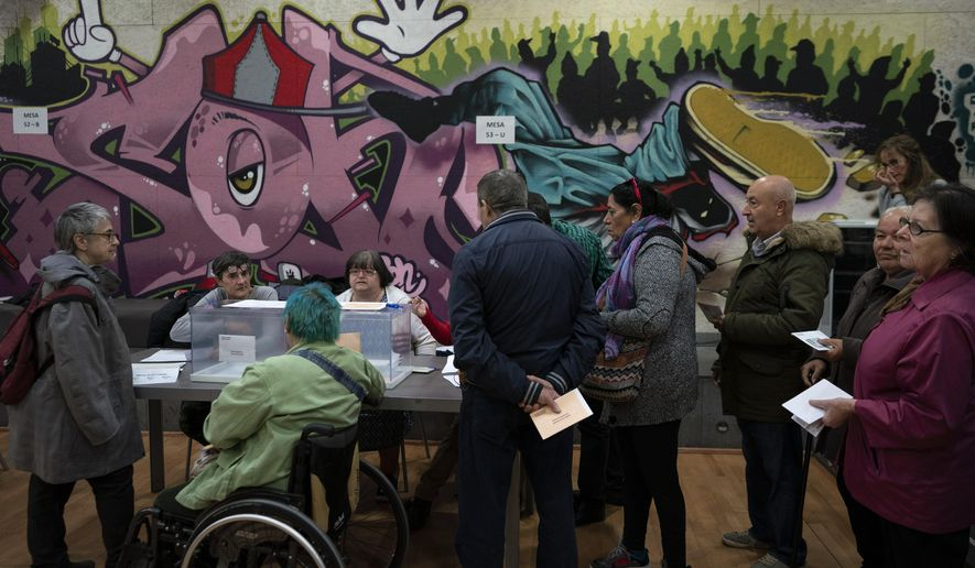 People line up in a polling station to cast their vote for the general election in Barcelona, Spain, Sunday, Nov. 10, 2019. Spain holds its second national election this year after Socialist leader Pedro Sanchez failed to win support for his government in a fractured Parliament. (AP Photo/Felipe Dana)