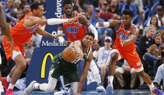 Milwaukee Bucks forward Giannis Antetokounmpo passes the ball away from Oklahoma City Thunder forward Darius Bazley, left, forward Nerlens Noel (9) and guard Hamidou Diallo, right, during the first half of an NBA basketball game Sunday, Nov. 10, 2019, in Oklahoma City. (AP Photo/Sue Ogrocki)