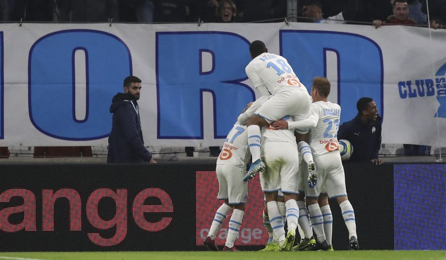 Marseille's Dimitri Payet celebrates with teammates after scoring his side's second goal during the French League One soccer match between Marseille and Lyon at the Velodrome stadium in Marseille, southern France, Sunday, Nov. 10, 2019. (AP Photo/Daniel Cole)