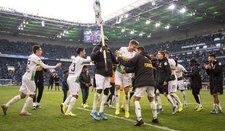 Moenchengladbach's team celebrates after winning the German Bundesliga soccer match between Borussia Moenchengladbach and Werder Bremen in Moenchengladbach, Sunday, Nov. 10, 2019. (Marius Becker/dpa via AP)
