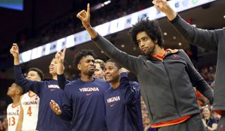 Virginia players on the bench react to a play during an NCAA college basketball game against James Madison in Charlottesville, Va., Sunday, Nov. 10, 2019. (AP Photo/Andrew Shurtleff)