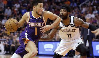 Phoenix Suns guard Devin Booker (1) drives past Brooklyn Nets guard Kyrie Irving (11) during the first half of an NBA basketball game Sunday, Nov. 10, 2019, in Phoenix. (AP Photo/Matt York)