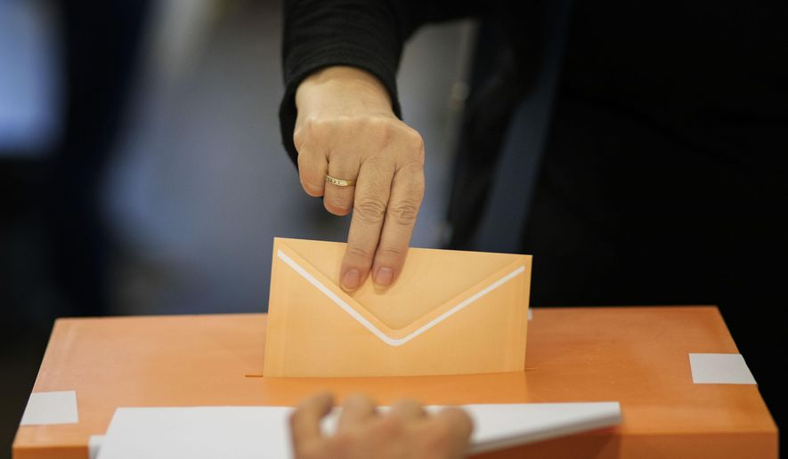 A woman casts her vote for the general election in Barcelona, Spain, Sunday, Nov.10, 2019. Spain holds its second national election this year after Socialist leader Pedro Sanchez failed to win support for his government in a fractured Parliament. (AP Photo/Emilio Morenatti)