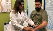 Iraq War veteran Zachary Muoz (right) receives a free checkup from Dr. Suneetha Budampati, executive physician for National Spine and Pain Centers in Arlington, Virginia, on Monday. Mr. Muoz lives with chronic back pain and incurred a traumatic brain injury when a bomb set off under his military vehicle in 2007. (Shen Wu Tan/ The Washington Times)