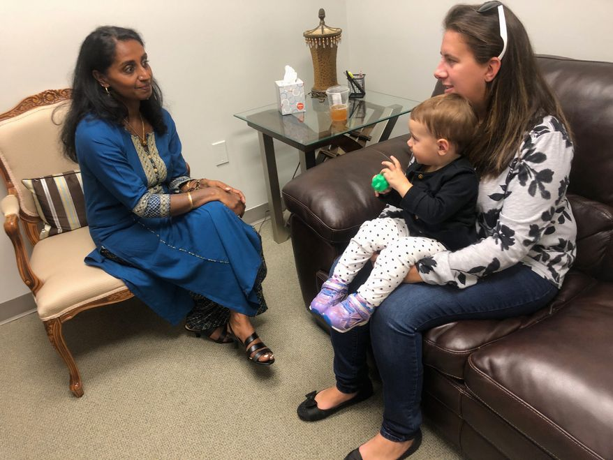 """Ranjani Johnson (left), a volunteer at Mosaic Virginia, counsels Holly Jenter, with her 16-month-old daughter, Tatum, as part of the crisis pregnancy center's """"Earn While You Learn"""" program. Mosaic Virginia celebrates its 25th anniversary Tuesday at the Hilton Washington Dulles Airport hotel in Herndon. (Carolyn Bolton/Special to The Washington Times)"""