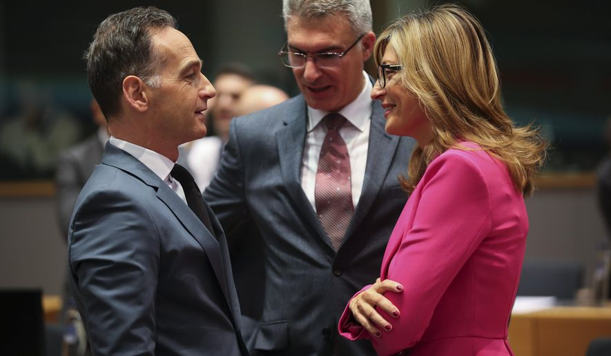 Germany's Foreign Minister Heiko Maas, left, talks to Bulgarian Foreign Minister Ekaterina Zaharieva, right, and Malta's Foreign Minister Carmelo Abela during an European Foreign Affairs Ministers meeting at the Europa building in Brussels, Monday, Nov. 11, 2019. European Union foreign ministers are discussing ways to keep the Iran nuclear deal intact after the Islamic Republic began enrichment work at its Fordo power plant. (AP Photo/Francisco Seco)