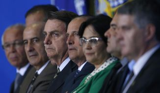 Brazil's President Jair Bolsonaro, center, and his ministers attend the launch of the Green and Yellow program to create formal jobs for young people, at the Planalto Presidential Palace, in Brasilia, Brazil, Monday, Nov. 11, 2019. (AP Photo/Eraldo Peres)