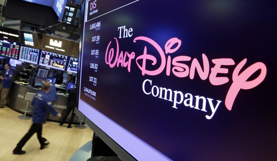 In this Aug. 8, 2017, file photo, The Walt Disney Co. logo appears on a screen above the floor of the New York Stock Exchange. On Tuesday, Nov. 12, Disney Plus launches its streaming service. (AP Photo/Richard Drew, File)