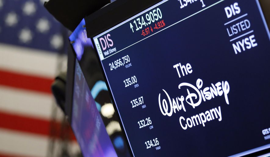 In this Aug. 7, 2019, file photo the logo for The Walt Disney Company appears above a trading post on the floor of the New York Stock Exchange. On Tuesday, Nov. 12, Disney Plus launches its streaming service. (AP Photo/Richard Drew, File)